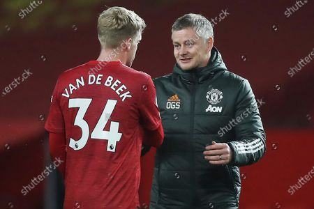Manchester United's manager Ole Gunnar Solskjaer, right, and Donny van der Beek celebrate after their team won the English Premier League soccer match between Manchester United and West Bromwich Albion at the Old Trafford stadium in Manchester, England