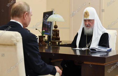 Russian President Vladimir Putin listens to Russian Orthodox Church Patriarch Kirill during their meeting at the Novo-Ogaryovo residence outside Moscow, Russia