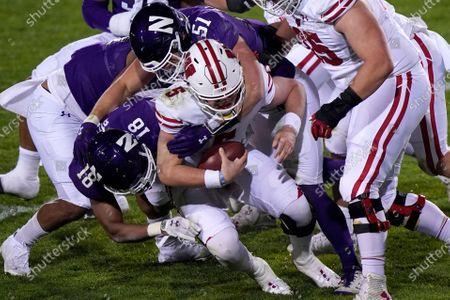 Wisconsin quarterback Graham Mertz (5) is sacked by Northwestern cornerback Cam Ruiz, left, and linebacker Blake Gallagher during the second half of an NCAA college football game in Evanston, Ill., . Northwestern won 17-7