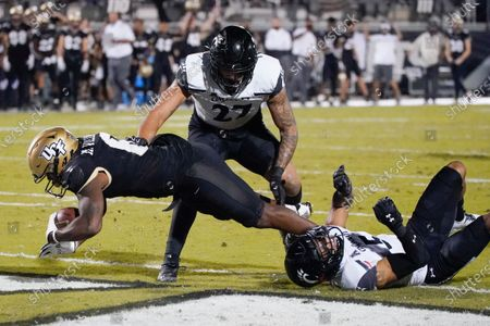 Central Florida wide receiver Marlon Williams, left, scores a touchdown as he gets past Cincinnati linebacker Darrian Beavers, center, and safety Darrick Forrest, right, during the second half of an NCAA college football game, in Orlando, Fla