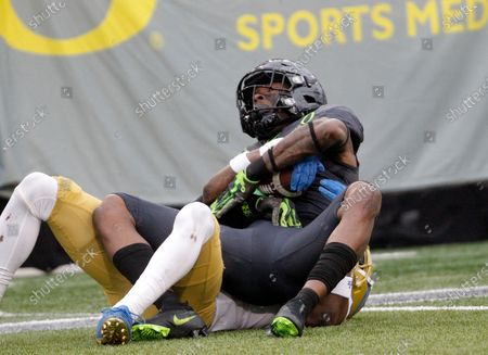 Stock Photo of Oregon Ducks wide receiver Johnny Johnson III (3) makes sure he keeps possession of the football after being taken down after a pass reception during the NCAA football game between the Oregon Ducks and the UCLA Bruins at Autzen Stadium, Eugene, OR. Larry C (Cal Sport Media via AP Images)