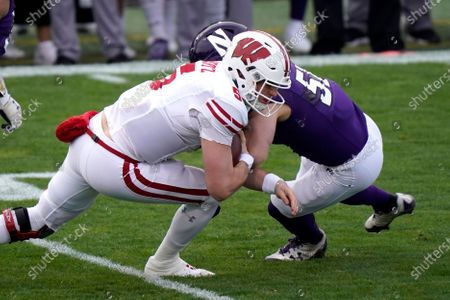 Wisconsin quarterback Graham Mertz, left, is tackled by Northwestern linebacker Blake Gallagher during the first half of an NCAA college football game in Evanston, Ill