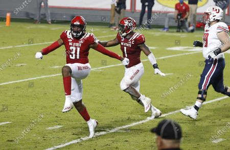 Stock Image of North Carolina State's Vi Jones (31) and Isaiah Moore (1) celebrate after Jones blocked a field goal-attempt by Liberty's Alex Barbir during the second half of an NCAA college football game, in Raleigh, N.C