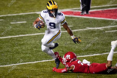 Michigan's Chris Evans (9) avoids a tackle attempt by Rutgers' Tre Avery (21) during the first half of an NCAA college football game, in Piscataway, N.J