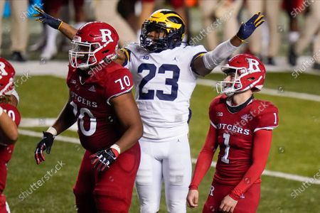 Rutgers' Valentino Ambrosio (1) and teammate Reggie Sutton (70) react as Michigan's Michael Barrett celebrates Ambrosio missing a field goal in overtime of an NCAA college football game, in Piscataway, N.J. Michigan won 48-42