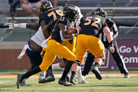 Southern Mississippi running back Dee Baker (23) runs behind offensive linemen Tykeem Doss (79) and Louis Smith (52) during an NCAA college football game, in Hattiesburg, Miss. UTSA won 23-20