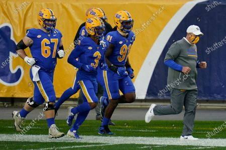 Pittsburgh head coach Pat Narduzzi comes on the field with Pittsburgh defensive back Damar Hamlin (3), defensive lineman Patrick Jones II (91), quarterback Kenny Pickett (8) and offensive lineman Jimmy Morrissey (67) for the start of an NCAA college football game against Virginia Tech, in Pittsburgh
