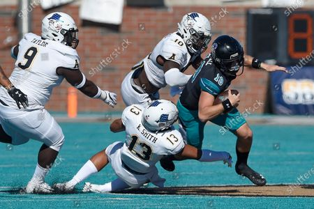 Stock Image of Coastal Carolina quarterback Grayson McCall (10) runs out of the pocket pursued by Appalachian State's (l-r) Demetrius Taylor, Kaiden Smith, and Tim Frizzell during the second half of an NCAA college football game, in Conway, S.C. Coastal Carolina won 34-23