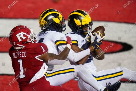 Michigan's Daxton Hill, right, intercepts a pass to Rutgers' Isaih Pacheco, left, as teammate Vincent Gray, center, defends during the third overtime of an NCAA college football game, in Piscataway, N.J. Michigan won 48-42