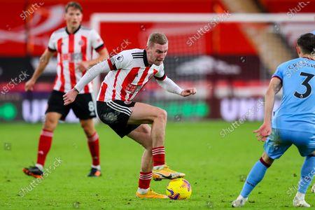 Oli McBurnie of Sheffield United looks for a way around Aaron Cresswell of West Ham United