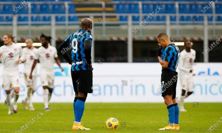 Inter Milan's Romelu Lukaku, left, and Inter Milan's Alexis Sanchez stand after Torino's Cristian Ansaldi scored during the Serie A soccer match between Inter Milan and Torino at the San Siro Stadium, in Milan, Italy