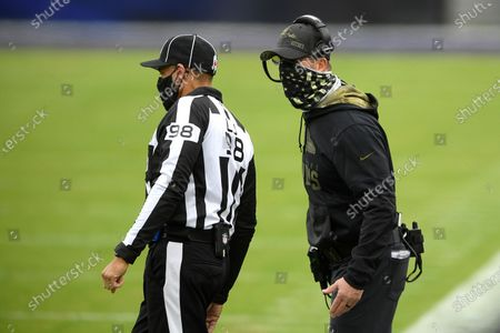 Stock Image of Baltimore Ravens head coach John Harbaugh, right, talks with head linesman Greg Bradley (98) during the first half of an NFL football game against the Tennessee Titans, in Baltimore