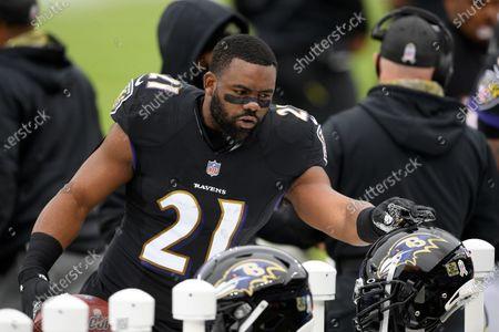 Baltimore Ravens running back Mark Ingram (21) arranges his helmet before an NFL football game against the Tennessee Titans, in Baltimore