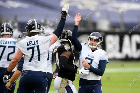 Tennessee Titans kicker Stephen Gostkowski (3) celebrates a field goal with offensive tackle Dennis Kelly (71) during the first half of an NFL football game against the Baltimore Ravens, in Baltimore