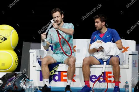 Wesley Koolhof of the Netherlands, left, applys grip to his racquet with Nikola Mektic of Croatia, right, during a break as they play against Jurgen Melzer of Austria and Edouard Roger-Vasselin of France during their doubles final tennis match at the ATP World Finals tennis tournament at the O2 arena in London