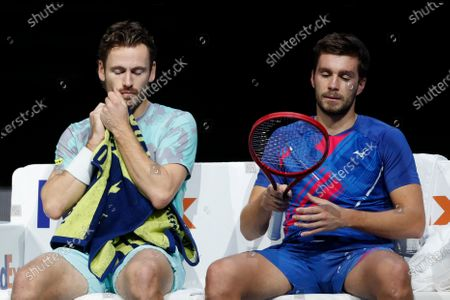 Wesley Koolhof of the Netherlands, left, and Nikola Mektic of Croatia, right, sit during a break as they play against Jurgen Melzer of Austria and Edouard Roger-Vasselin of France during their doubles final tennis match at the ATP World Finals tennis tournament at the O2 arena in London