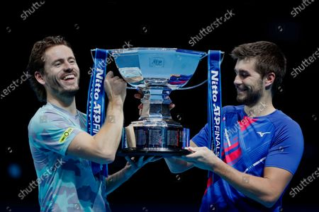 Wesley Koolhof of the Netherlands, left, and Nikola Mektic of Croatia, right, hold up the trophy after winning against Jurgen Melzer of Austria and Edouard Roger-Vasselin of France during their doubles final tennis match at the ATP World Finals tennis tournament at the O2 arena in London