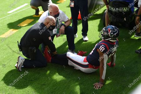 Houston Texans wide receiver Randall Cobb (18) is checked for an injury following his touchdown catch against the New England Patriots during the first half of an NFL football game, in Houston