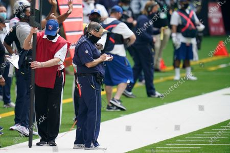 New England Patriots head coach Bill Belichick takes notes during an NFL football game against the Houston Texans, in Houston