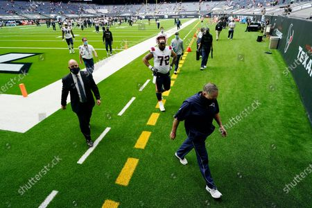 New England Patriots head coach Bill Belichick, right, walks off the field after the team's loss to the Houston Texans in an NFL football game, in Houston