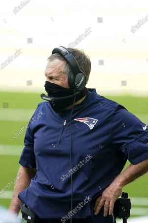 New England Patriots head coach Bill Belichick wears a face mask as he looks on from the sideline during an NFL football game against the Houston Texans, in Houston