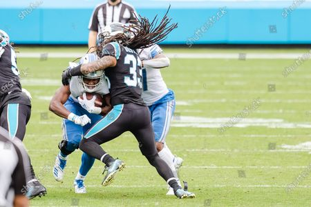 Detroit Lions running back Adrian Peterson (28) drives into Carolina Panthers free safety Tre Boston (33) in the NFL matchup at Bank of America Stadium in Charlotte, NC