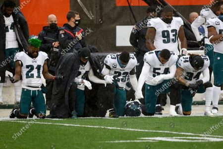 Philadelphia Eagles safety Jalen Mills (21), cornerback Darius Slay (24), safety Rodney McLeod (23), linebacker Shaun Bradley (54) and Philadelphia Eagles cornerback Cre'Von LeBlanc (34) kneel during the playing of the national anthem prior to the start of an NFL football game against the Cleveland Browns, in Cleveland