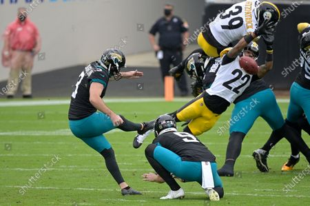 Jacksonville Jaguars place kicker Chase McLaughlin (3) kicks a field goal in front of Pittsburgh Steelers cornerback Steven Nelson (22) and safety Minkah Fitzpatrick (39) during the first half of an NFL football game, in Jacksonville, Fla