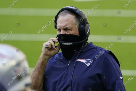 New England Patriots head coach Bill Belichick wears a face mask on the sidelines during the first half of an NFL football game against the Houston Texans, in Houston