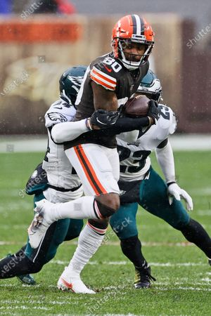 Cleveland Browns wide receiver Jarvis Landry (80) is tackled by Philadelphia Eagles cornerback Darius Slay (24) and free safety Rodney McLeod (23) during the first half of an NFL football game, in Cleveland