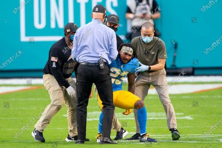 Los Angeles Chargers head coach Anthony Lynn (left) and staff help an injured Los Angeles Chargers safety Rayshawn Jenkins (23) up off the field as the Chargers take on the Miami Dolphins during an NFL football game, in Miami Gardens, Fla