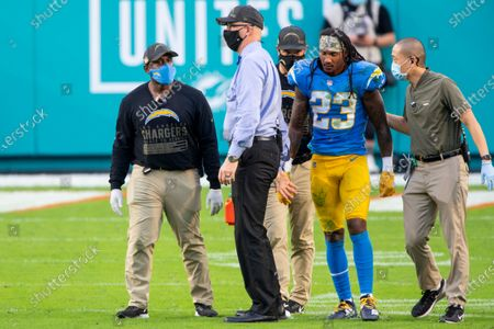 Stock Image of Los Angeles Chargers head coach Anthony Lynn (left) and staff help an injured Los Angeles Chargers safety Rayshawn Jenkins (23) up off the field as the Chargers take on the Miami Dolphins during an NFL football game, in Miami Gardens, Fla