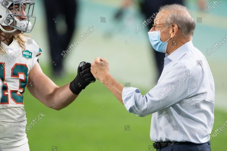 Miami Dolphins linebacker Andrew Van Ginkel (43) bumps fists with Miami Dolphins Chairman of the Board/Managing General Partner Stephen Ross on the field after the Dolphins defeated the Los Angeles Chargers during an NFL football game, in Miami Gardens, Fla