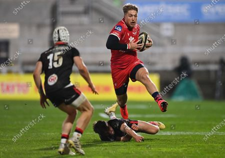 Stock Image of Tyler Morgan of Scarlets evades the tackle of Ulster's Bill Johnston