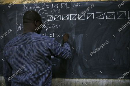 An electoral official writes counting results on a chalkboard as counting of the votes started after the closing of a polling station during the first round of the presidential election in Ouagadougou, Burkina Faso, 22 November 2020. Polls opened on 22 November for Burkina Faso presidential elections, in which the incumbent Roch Marc Christian Kabore is expected to secure a second mandate. Some 6,5 million people are eligible to vote in the race that pits Kabore, 63, against main challenger Zephirin Diabre, 61.