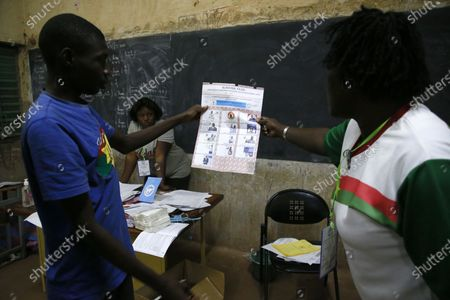 An electoral official holds up a ballot as counting of the votes started after the closing of a polling station during the first round of the presidential election in Ouagadougou, Burkina Faso, 22 November 2020. Polls opened on 22 November for Burkina Faso presidential elections, in which the incumbent Roch Marc Christian Kabore is expected to secure a second mandate. Some 6,5 million people are eligible to vote in the race that pits Kabore, 63, against main challenger Zephirin Diabre, 61.