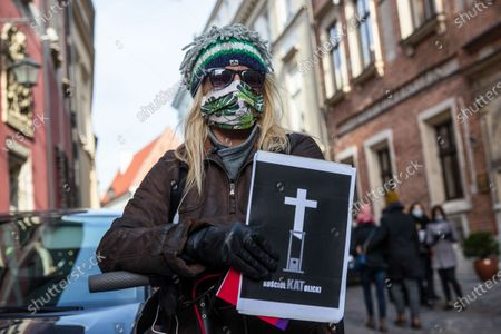 A protester wearing a face mask holds a placard during the demonstration.Hundreds of people protested on Kanoniczna Street in Cracow. The protest was an aftermath of a recently released reportage 'Don Stanislao. The second face of cardinal Dziwisz' that indicated that cardinal Dziwisz, long-time aide of pope John Paul II, could be responsible for covering up cases of pedophilia among catholic priests. People gathered on the street demanding explanations from the church and expressed support for the victims of pedophilia.