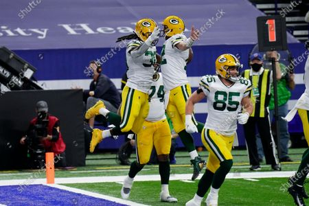 Green Bay Packers running back Jamaal Williams (30) and quarterback Aaron Rodgers (12) celebrate a touchdown during the first half of an NFL football game against the Indianapolis Colts, in Indianapolis