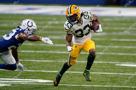 Green Bay Packers' Aaron Jones (33) runs against Indianapolis Colts' Kenny Moore II (23) during the first half of an NFL football game, in Indianapolis