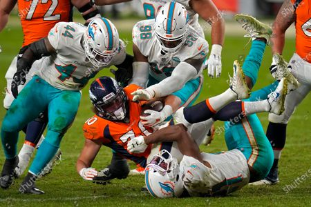 Denver Broncos running back Phillip Lindsay (30) is hit by Miami Dolphins free safety Eric Rowe (21) as outside linebacker Elandon Roberts (44) and defensive tackle Raekwon Davis (98) defend during the second half of an NFL football game, in Denver. The Broncos won 20-13