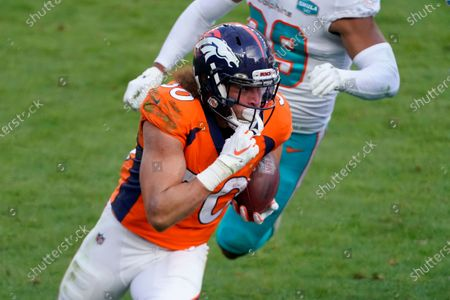 Stock Photo of Denver Broncos running back Phillip Lindsay (30) runs as Miami Dolphins free safety Brandon Jones pursues during the first half of an NFL football game, in Denver