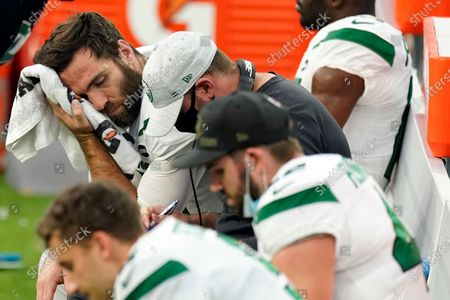 New York Jets quarterback Joe Flacco, top right, wipes sweat off his face during the second half of an NFL football game against the Los Angeles Chargers, in Inglewood, Calif