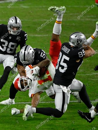 Kansas City Chiefs wide receiver Demarcus Robinson (11) is tackled by Las Vegas Raiders middle linebacker Raekwon McMillan (54) and tight end Derek Carrier (85) during the second half of an NFL football game, in Las Vegas