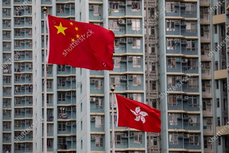 The People's Republic of China flag (L) and the Hong Kong SAR flag (R) are displayed outside the West Kowloon Law Courts building in Hong Kong, China, 23 November 2020. Three pro-democracy activists, Joshua Wong Chi-fung, Ivan Lam Long Ying, and Agnes Chow Ting, have been charged for incitement to knowingly take part in an unauthorised assembly, organising an unauthorised assembly and knowingly taking part in an unauthorised assembly.