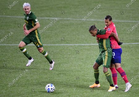 Dallas midfielder Andres Ricaurte, right, holds up Portland Timbers forward Andy Polo, center, as Portland Timbers midfielder Cristhian Paredes, left, looks on during the second half of an MLS soccer match in Portland, Ore., . Dallas won the match in penalty kicks