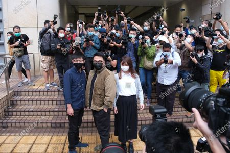 Pro-democracy activists (L-R) Agnes Chow, Ivan Lam and Joshua Wong arrive wearing face masks at the West Kowloon Magistrates' Court for charges in connection with a protest outside police headquarters in June 2019 .