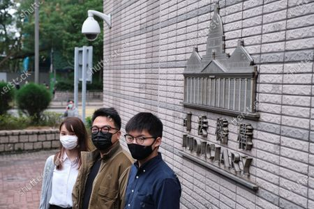 Pro-democracy activists (L-R) Agnes Chow, Ivan Lam and Joshua Wong wearing face masks pose for photos as they arrive at West Kowloon Magistrates' Court for charges in connection with a protest outside police headquarters in June 2019 .