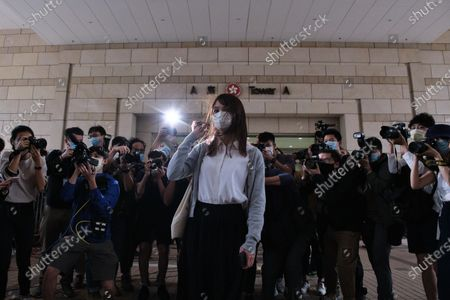 Pro-democracy activist Agnes Chow wearing a face mask poses for photos as she arrives at the West Kowloon Magistrates' Court along with Joshua Wong and Ivan Lam for charges in connection with a protest outside police headquarters in June 2019 .