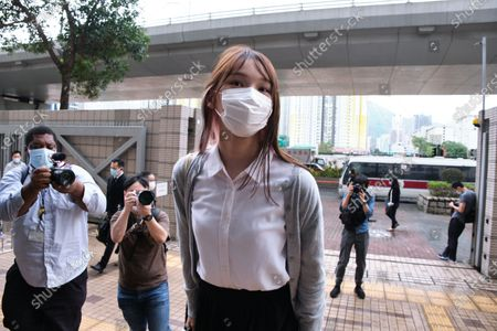 Pro-democracy activist Agnes Chow wearing a face mask arrives at the West Kowloon Magistrates' Court along with Joshua Wong and Ivan Lam for charges in connection with a protest outside police headquarters in June 2019 .