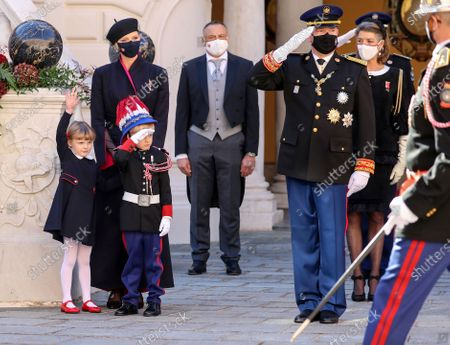 Prince Albert II of Monaco (R) and Prince Jacques of Monaco (3L) salute next to Princess Charlene of Monaco (2L) and Princess Gabriella of Monaco (L) during celebrations marking Monaco's National Day at the Palace in Monaco
